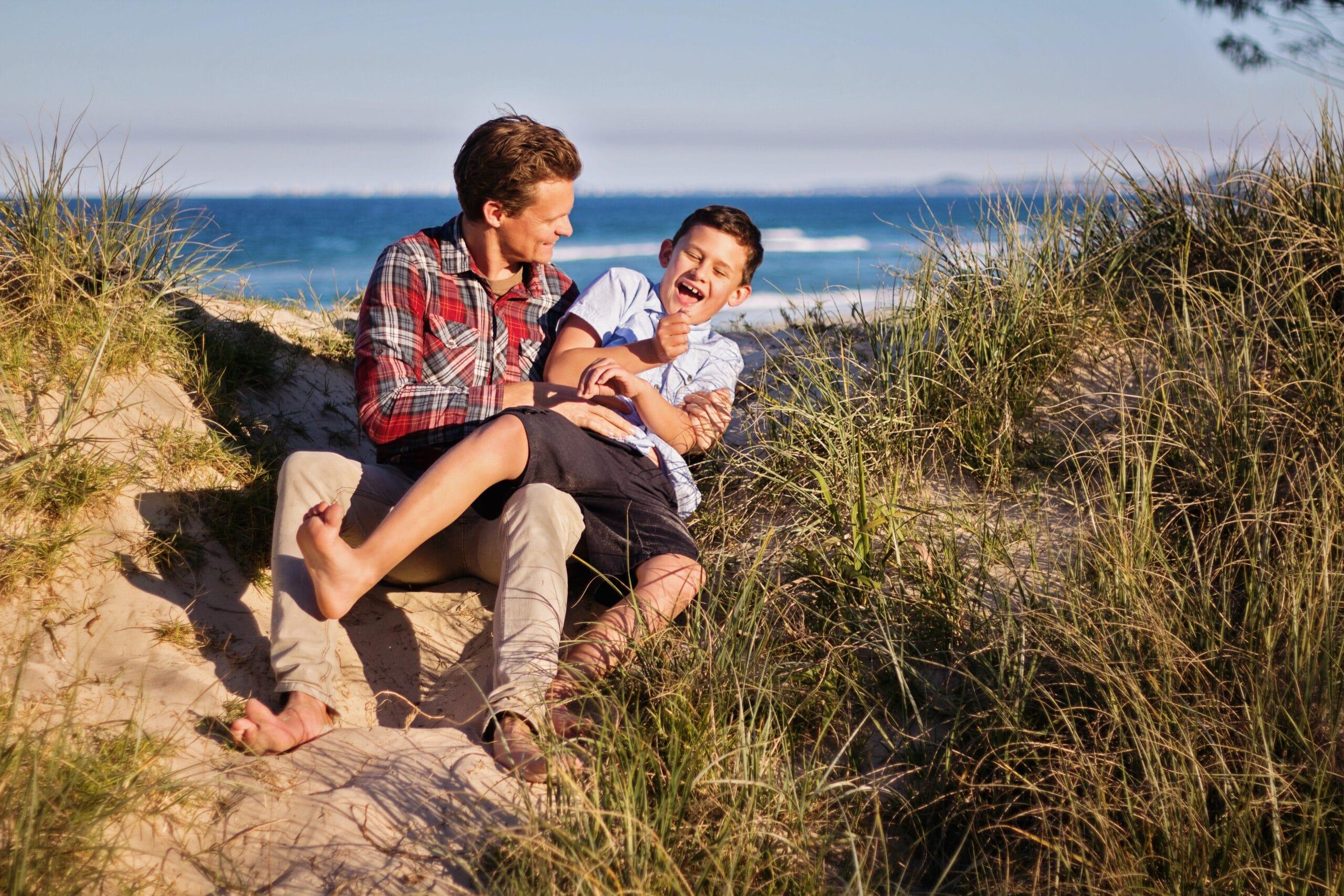 Vader speelt met zoon op het strand